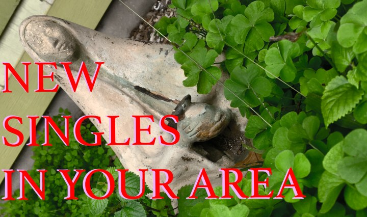 Text that says New Singles In Your Area on top of a photo showing a ceramic garden statue surrounded my clovers.