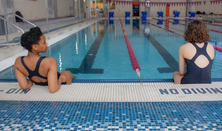 Two girls sitting a few feet apart at a swimming pool.