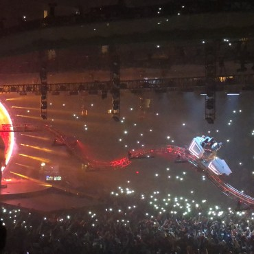 Travis Scott and a fan riding a rollercoaster over the crowd with a blow-up astronaut in the background.