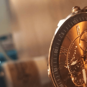 A gold watch resting on a brown wooden coffee table.