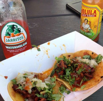 A pair of street tacos with a Jarritos and Cholula Hot Sauce bottle in the background.