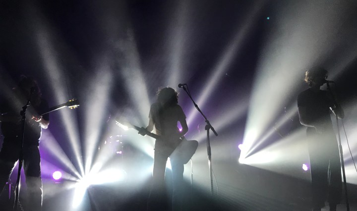The silhouette of the 3 frontmen of Car Seat Headrest play while white beams of light shoot towards the audience