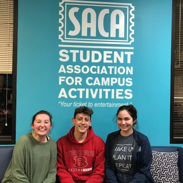 3 people sitting in front of the SACA Logo