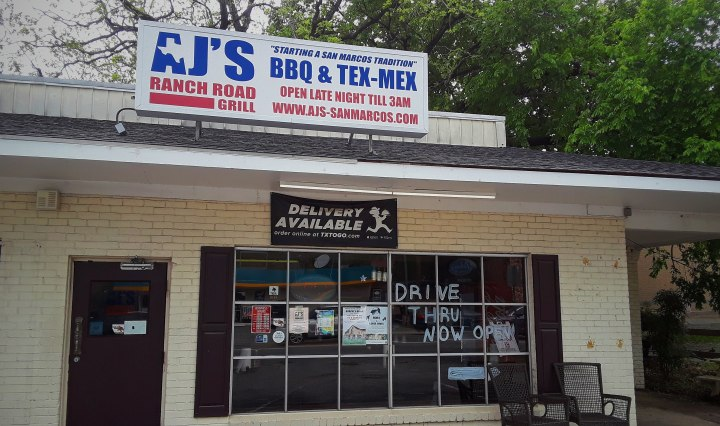"""The restaurant presides in a cream colored brick building with a sign over the entrance door that says """" AJ's Ranch Road Grill BBQ & Tex-Mex"""" in huge blue bolded letters."""