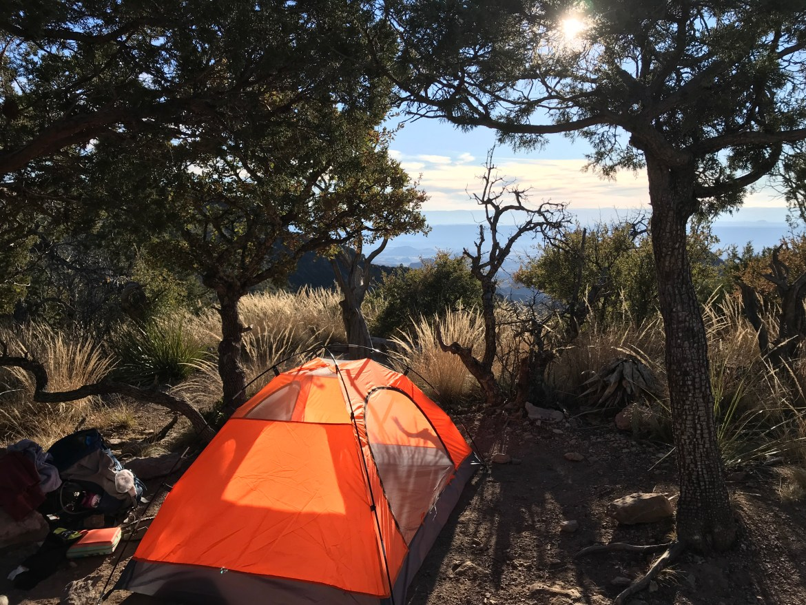 An orange tent with trees and mountains surrounding it.