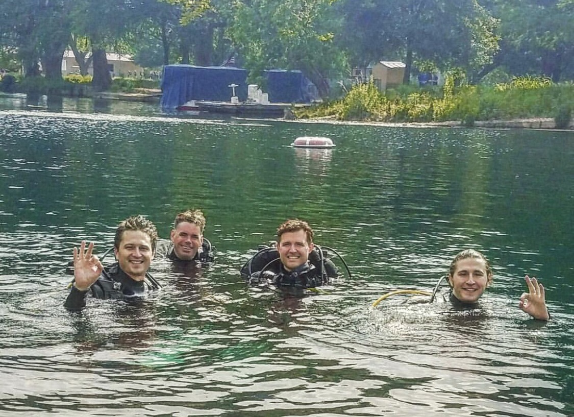 Four men in a river with Scuba gear on smiling.