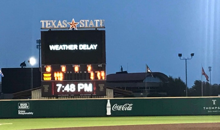 """Picture shows Texas State Jumbotron from the Baseball park. On the Jumbotron it says """"Weather Delay"""" to let the fans know that the game has been paused due to inclement weather"""