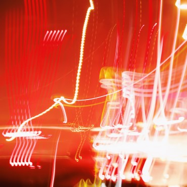 This photo is black, red, orange and yellow and displays lines and designs of light exposure done with a camera.