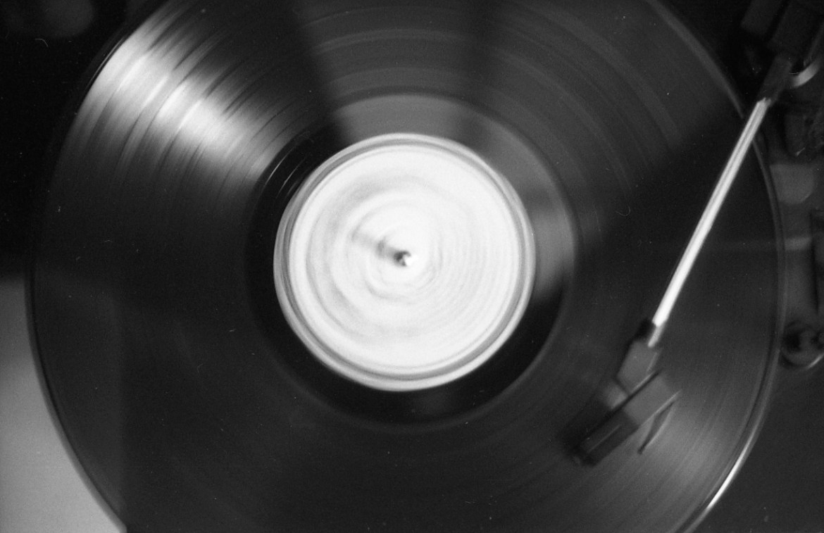 The black and white photo features a record player needle placed on a spinning vinyl.