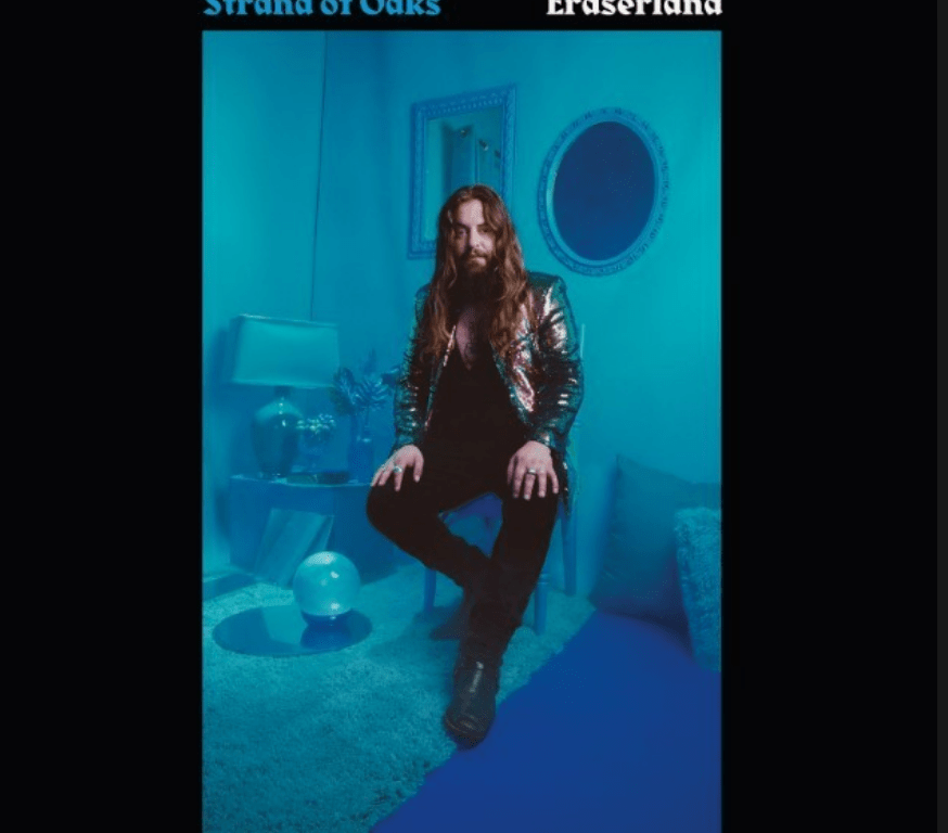 The image is a Caucasian man with long, wavy brown hair wearing black and a metallic brown jacket sitting on a stool. The setting is in a room where everything is tinted to a shade of blue while he keeps his regular color. There is a mirror and a picture frame behind him as well as a lamp, some pillows, and miscellaneous decor.