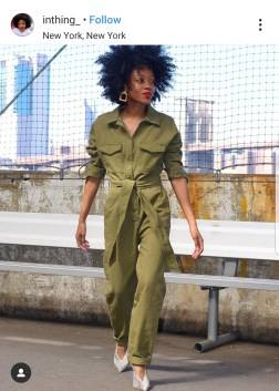 A woman wearing a green boiler suit with a fence background, with buildings in the distance.