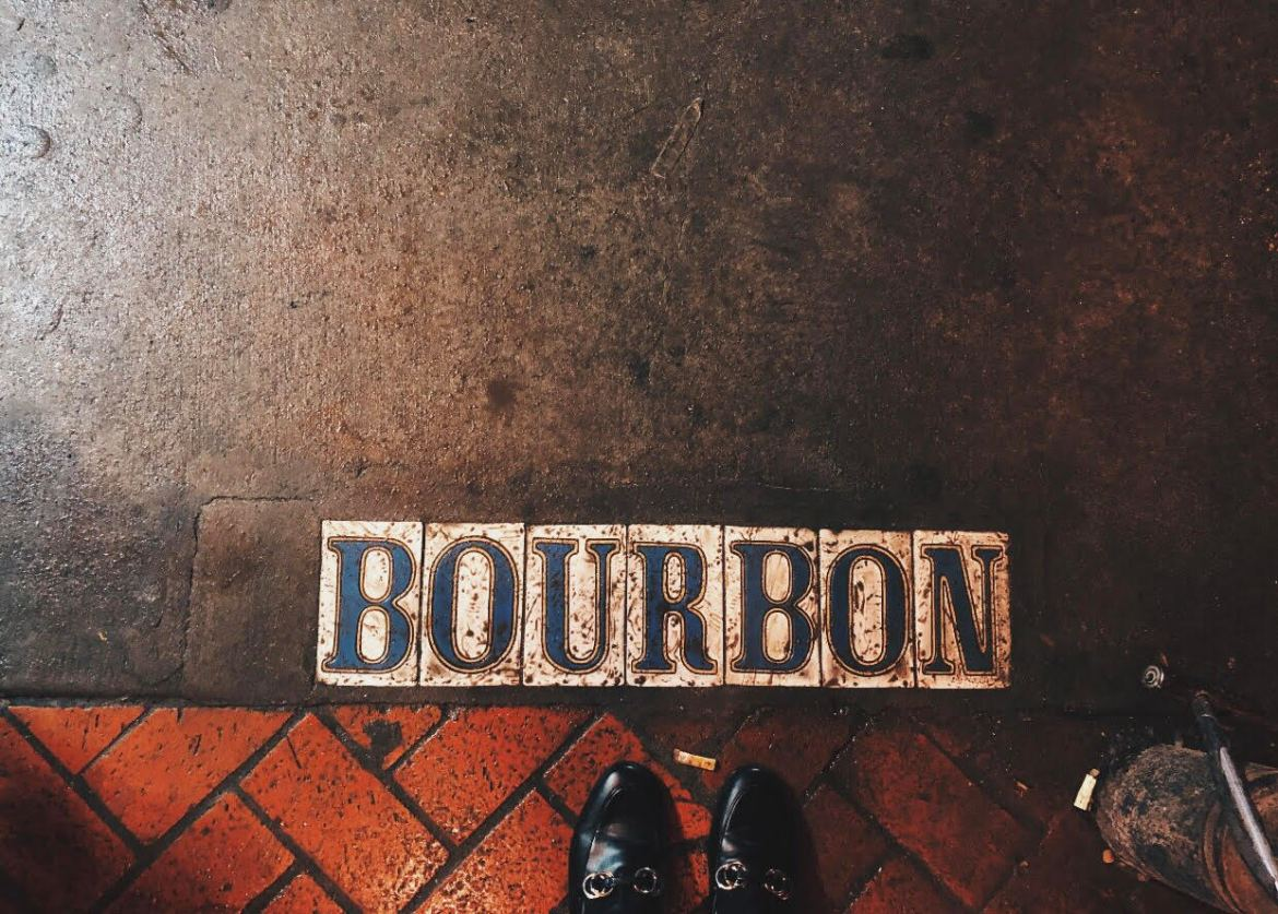 """A white and blue tiled """"Bourbon"""" sign on the sidewalk of New Orleans' Bourbon Street."""