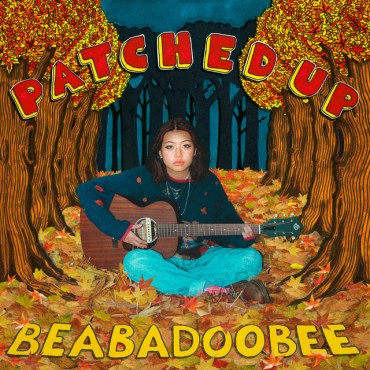 Bea Kristi holding a guitar, sitting on a pile of fallen autumn leaves. She's flanked by two-dimensional, hand drawn trees. The trees are questionable.