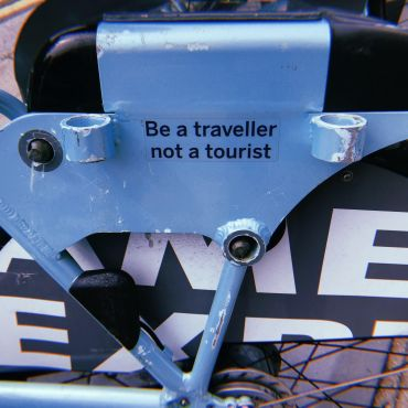 """A sticker that reads """"be a traveller, not a tourist"""" on a bike rack. Seen in Brighton, England."""
