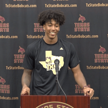 Man with black hair in Black & Gold shirt stands behind Texas State podium.