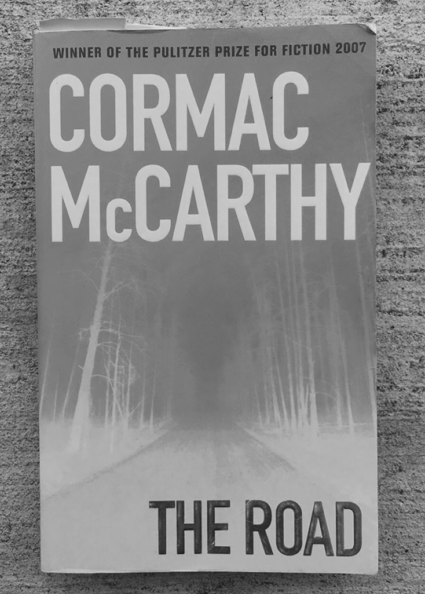 """Image of """"The Road"""" book cover on concrete. Edited to appear in black-and-white."""