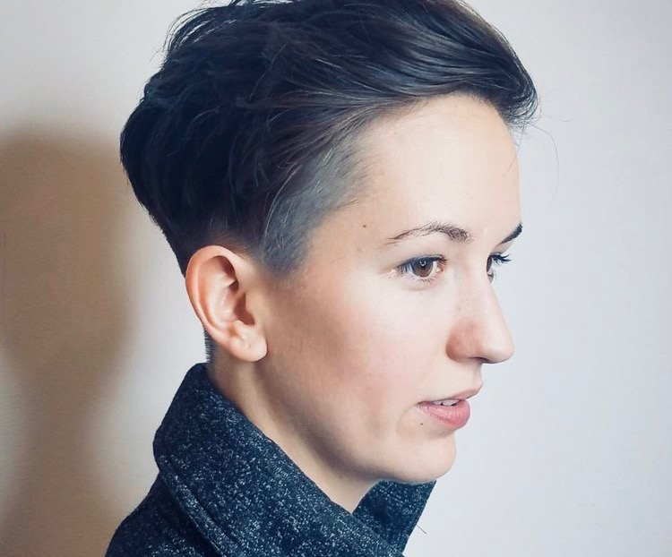 Girl with short hair against a gray background.