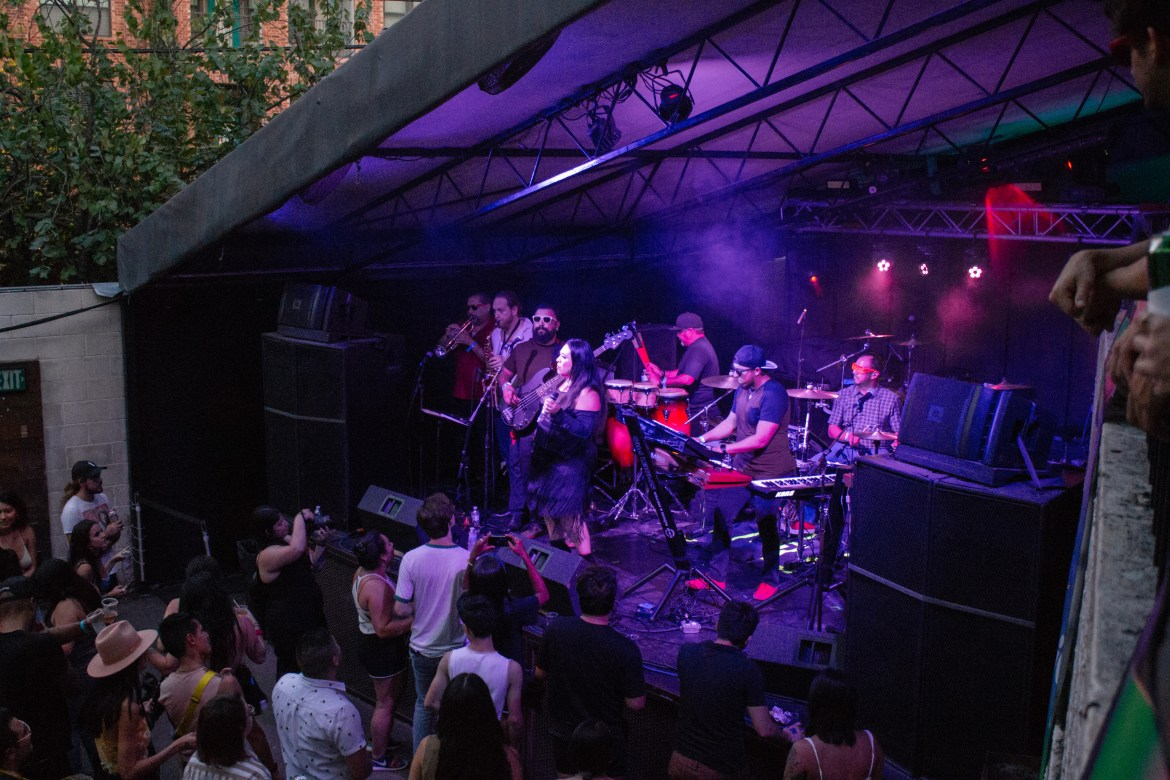 The horizontal photo features a band on stage as the audience watches