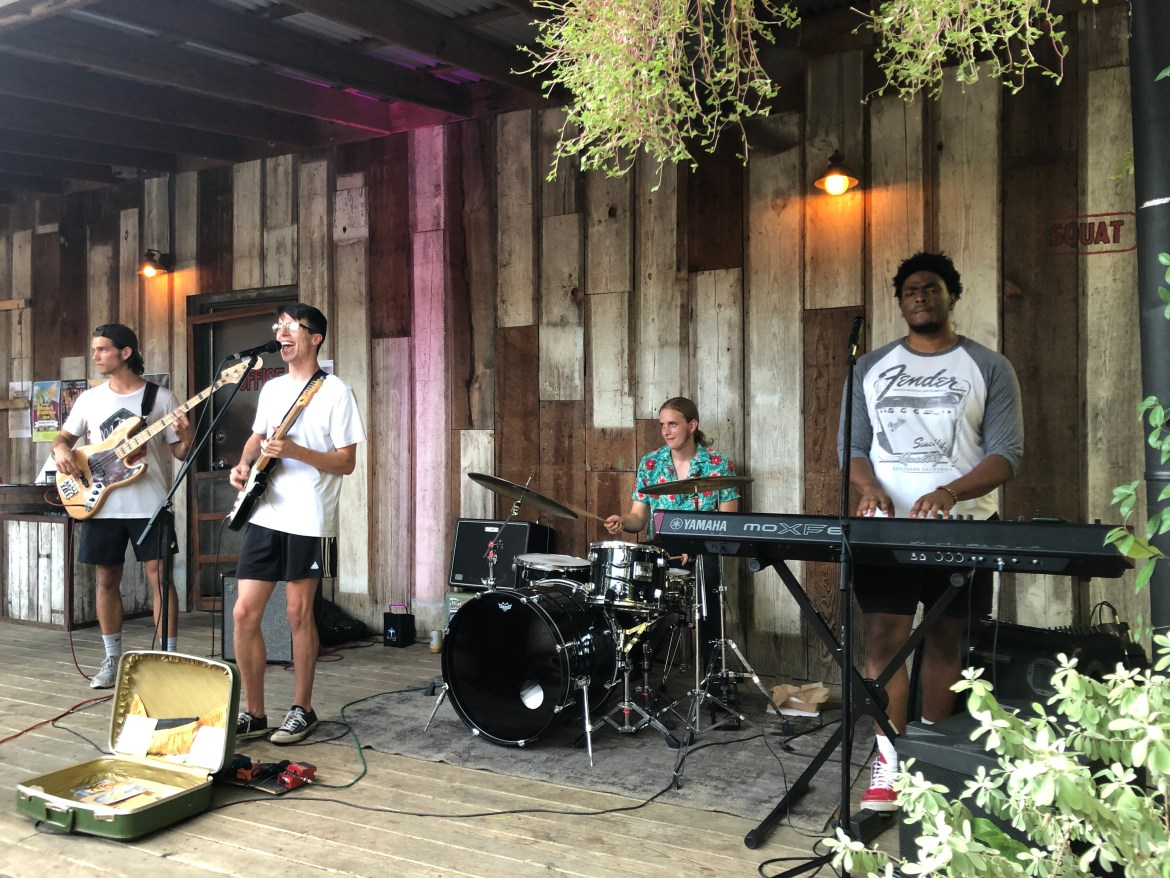 The four piece band is playing on a wooden stage outside in the back patio at Zelicks