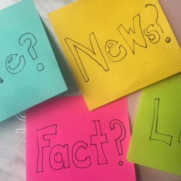 """four colorful sticky notes on a marbled background with one reading """"Fact?"""" another """"News?"""" another """"Fake?"""" another """"Lies?"""""""