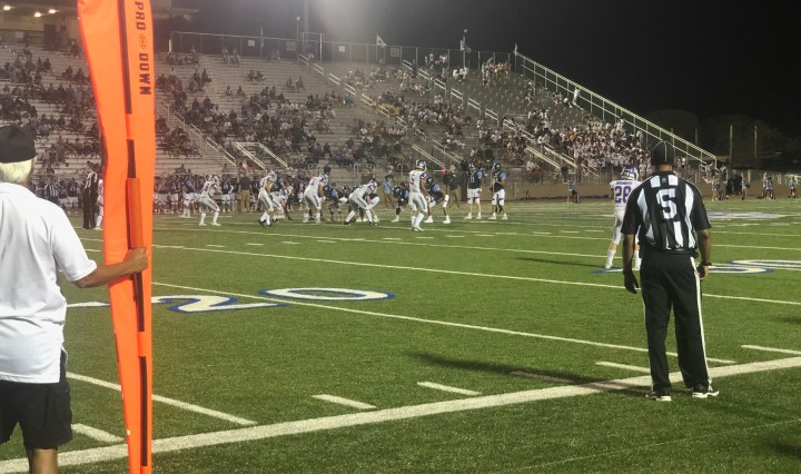 Pre-snap of a Jaguar play on the Rattler 36 yard-line. The Rattler defense is getting set on the line of scrimmage. The first down marker and a referee are visible in the picture watching the play.