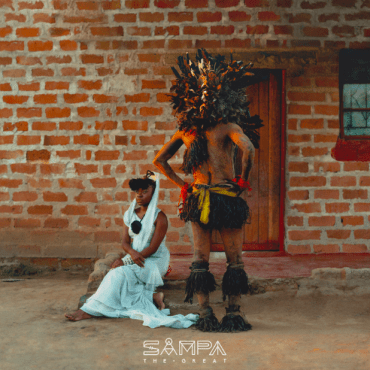 A colored image of Sampa sitting on the porch in a dress beside a man in tribal clothing.