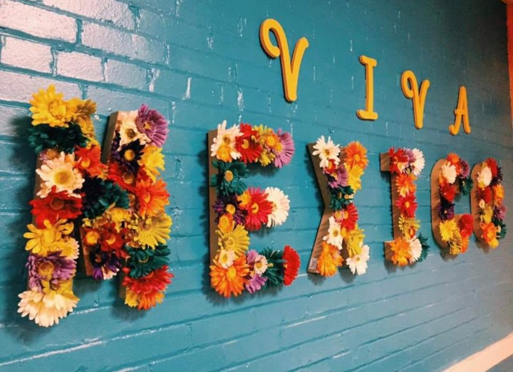 """A turquoise wall with """"Viva"""" in yellow and """"Mexico"""" in flowers"""