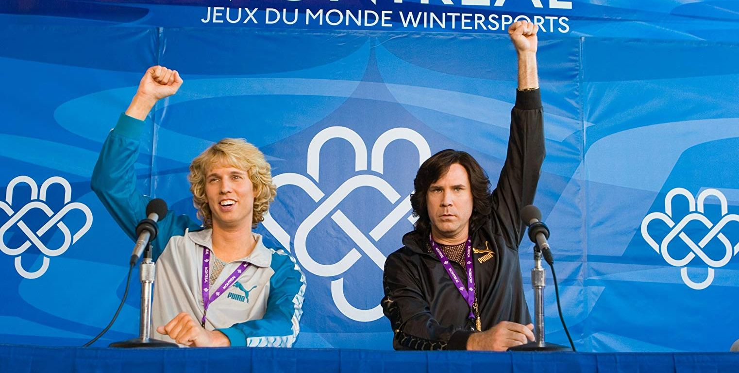 """Two men on a panel at a press conference after a figure skating competition, both holding their fists in the air with the title """"Montreal Jeux De Monde Wintersports"""" displayed behind them."""