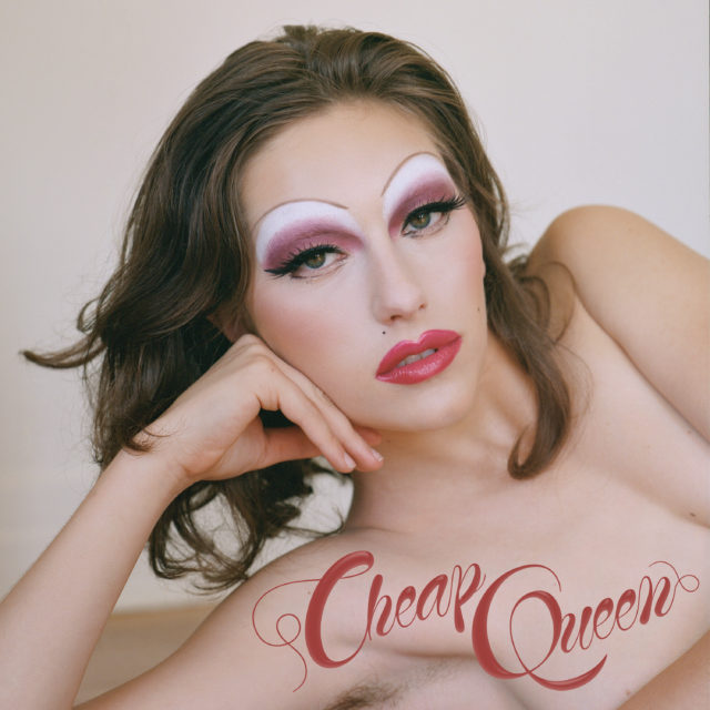 """Album cover hard showing King Princess laying down on her arm with drag makeup on, featuring pink and white eyeshadow. The words """"Cheap Queen"""" are placed at the bottom in red, cursive writing."""