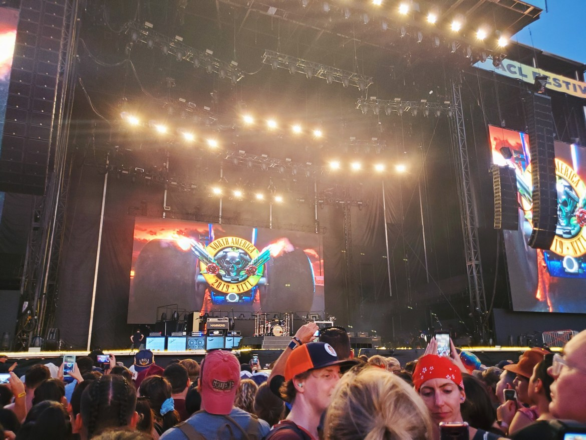 Guns N' Roses backdrop at the American Express stage in Zilker Park. The backdrop image is of a muscle car with the exhaust blowing out smoke and the back of the car has a skull with a gun at either side of it and roses at the base.