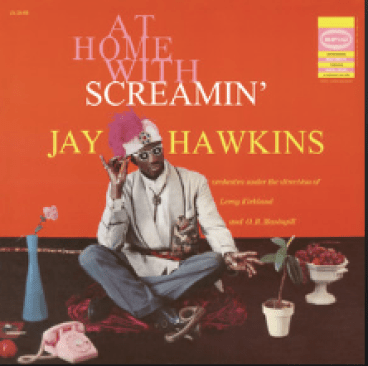 """Singer Screamin' Jay Hawkins sits Indian style against an orange background. He is surrounded by vases and flowers and wears a white and purple hat and sunglasses. The words """"At Home with Screamin' Jay Hawkins"""" reads in large font behind him."""
