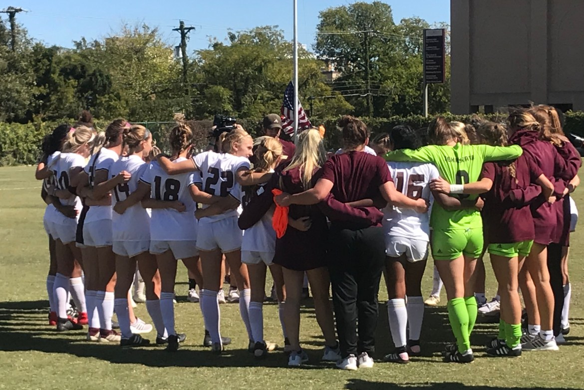 Bobcat soccer team in white jerseys join arm-in-arm in their final postgame circle of the regular season.
