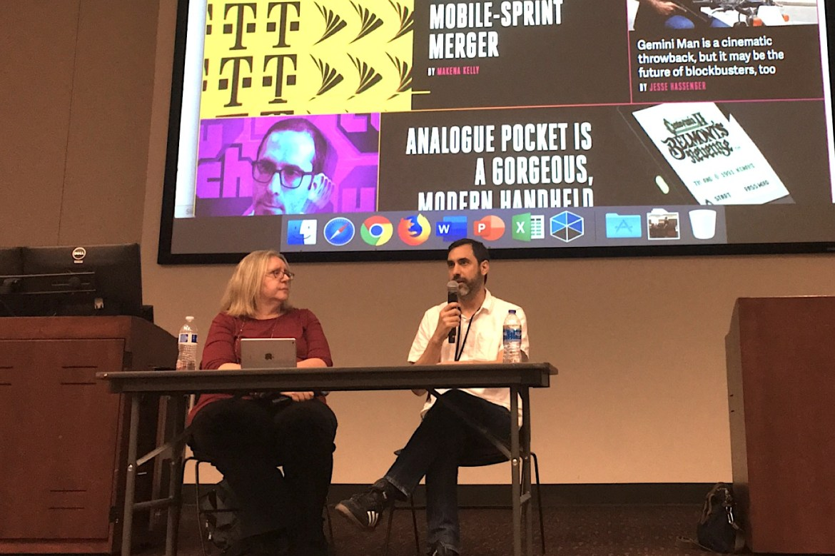 Pablo Mercado sitting at a table holding a microphone to his mouth. The Vox Media website is on the large screen behind him.