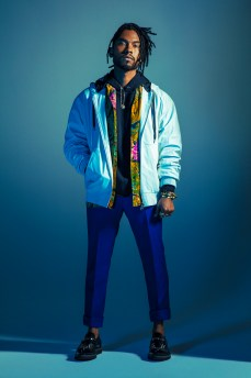 Singer Miguel standing with one hand out and one hand in his jacket pocket. The background is blue and he is standing in a spotlight.