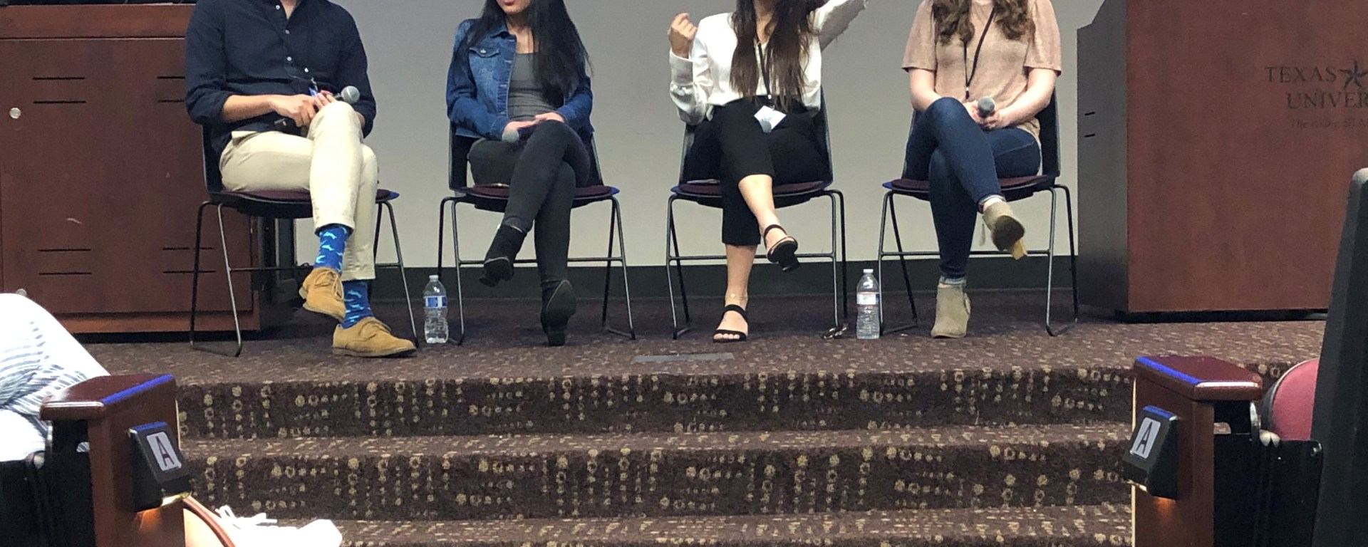 1 man and 3 women sit left to right in front of a auditorium of students on a stage.