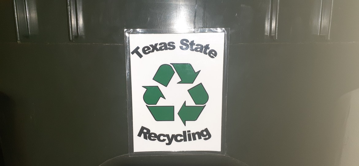 Green trash can with a recycling tag that says Texas State Recycling in black with a white paper background