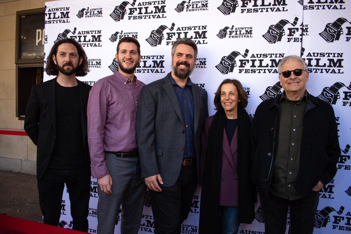 3 men stand next to eachother on the left and a woman stands in between the three men and one man on her right. They are all posing for a picture on the red carpet.