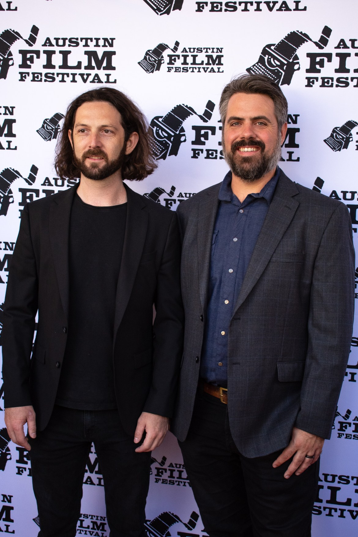 One man on the left is wearing all black and the one on the right wheres a gray suit jacket and a button down shirt. The two men are smiling.