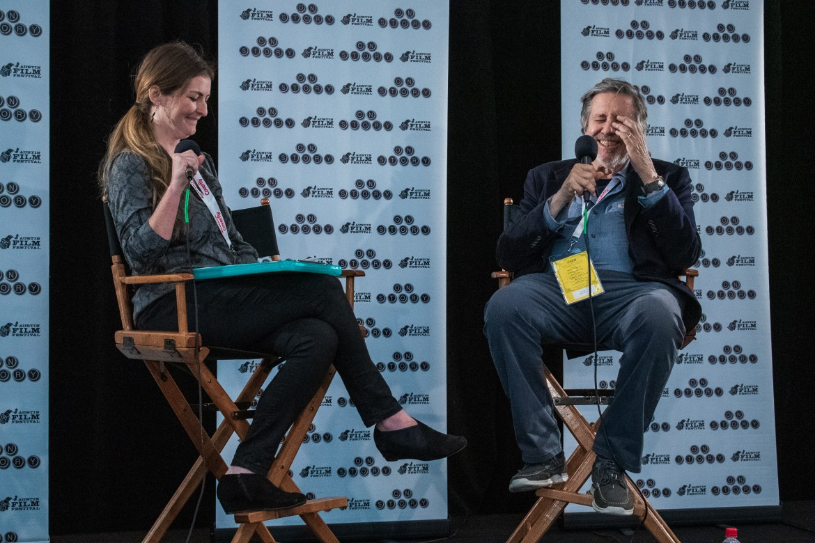 Man (right) and woman (left) laugh on stage while sitting in directors chairs and speaking into microphones.