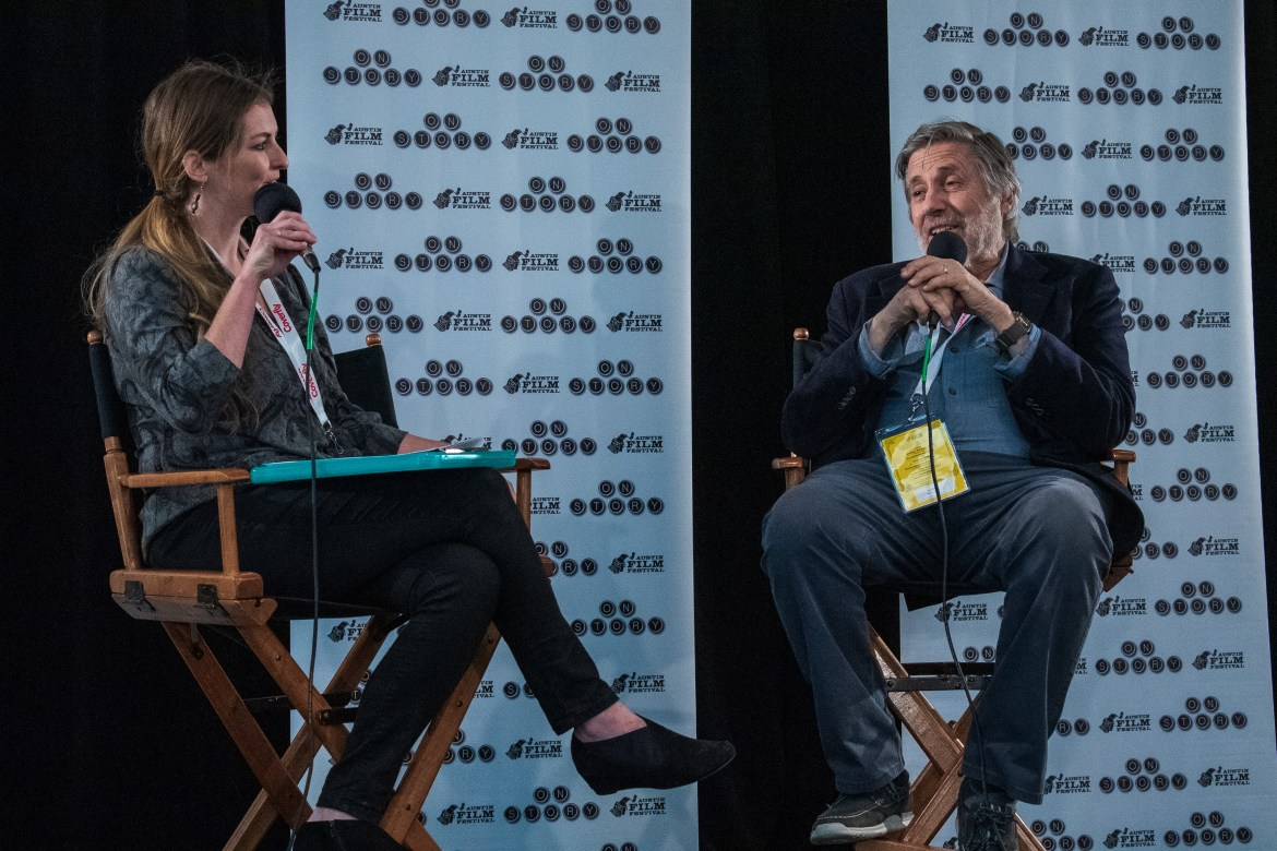 Man (left) and Woman (right) sit in directors chairs with mics in their hands.