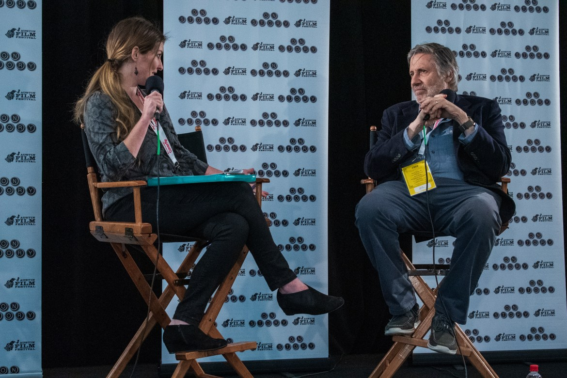 Man (left) and Woman (right) sit in directors chairs talking on microphones.