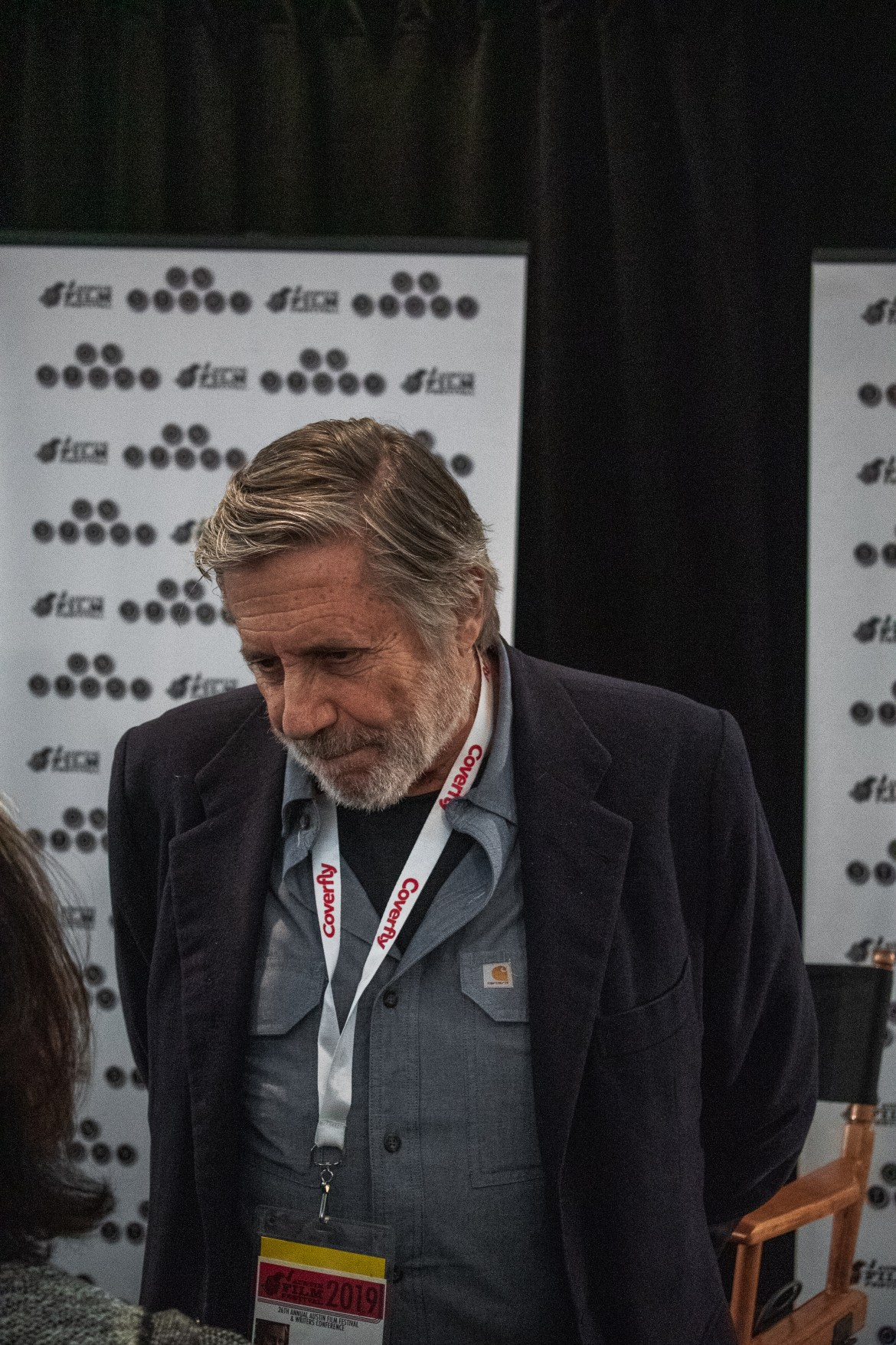 Man looking at a woman. He is wearing a navy suit jacket and a light blue button down with a press pass around his neck.