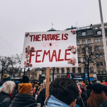 """A sign with """"the future is female"""" written on it with roses attached."""