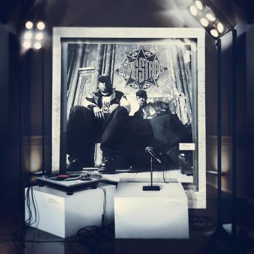 """Album art for Gangstarr """"One of the Best Yet"""", the cover shows a black and white framed picture of DJ Premier and Guru. A microphone and turn-table rest on white boxes in front of the image."""