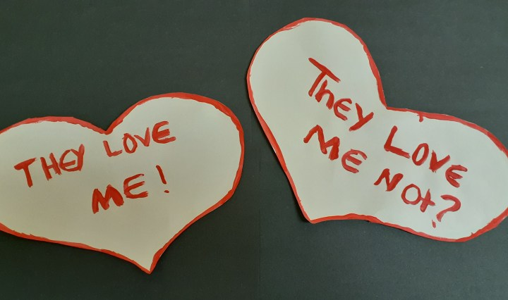 """Two white hearts outlined in red paint, one saying, """"They love me!"""" The other saying """"They love me not?"""" On a black background."""