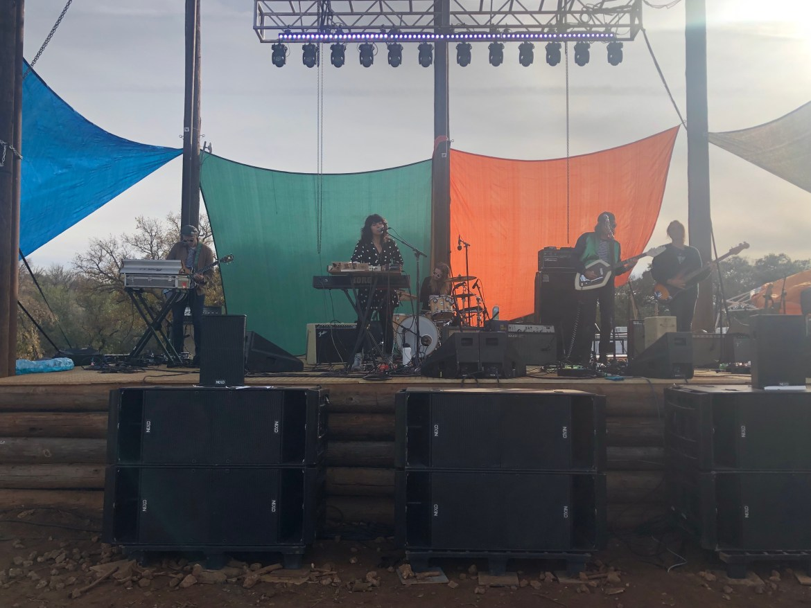 A band playing on stage in broad daylight with a blue, green, and orange curtain hanging behind them.