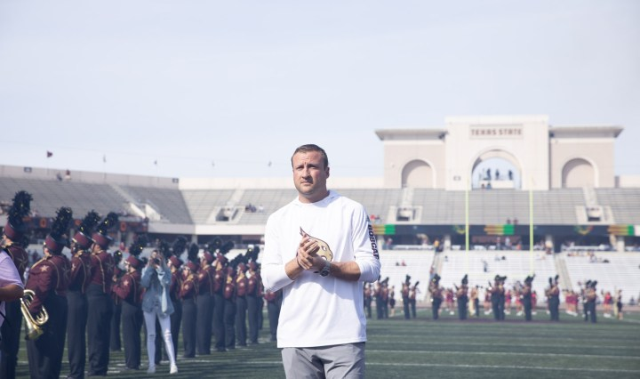Jake Spavital stands on the field, looking towards the camera at the end zone complex with the Texas State Marching Band lines the field behind him.