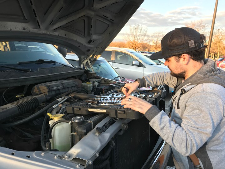 A silver truck has its hood lifted, revealing the engine within. A Texas State student looms over the engine, their toolset placed on the truck off to their left.