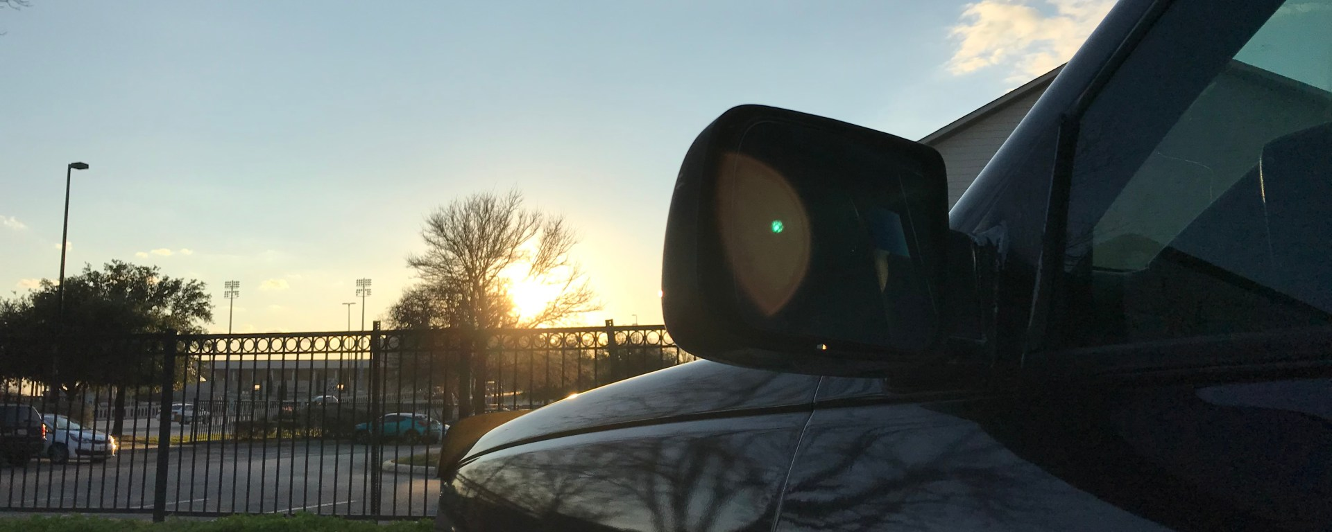 The front of a truck sits off to the right; a building behind it blocks some of the sun's setting rays.
