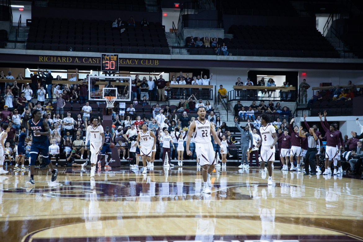 Senior Nijal Pearson celebrates after hitting a three-pointer in the loss against UTSA. Both teams are seen running back to the other side of the court, and the fans are standing up to cheer in the background.
